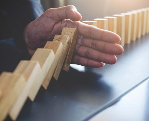 Foto Geschäftsmann stoppt Dominoeffekt mit Hand